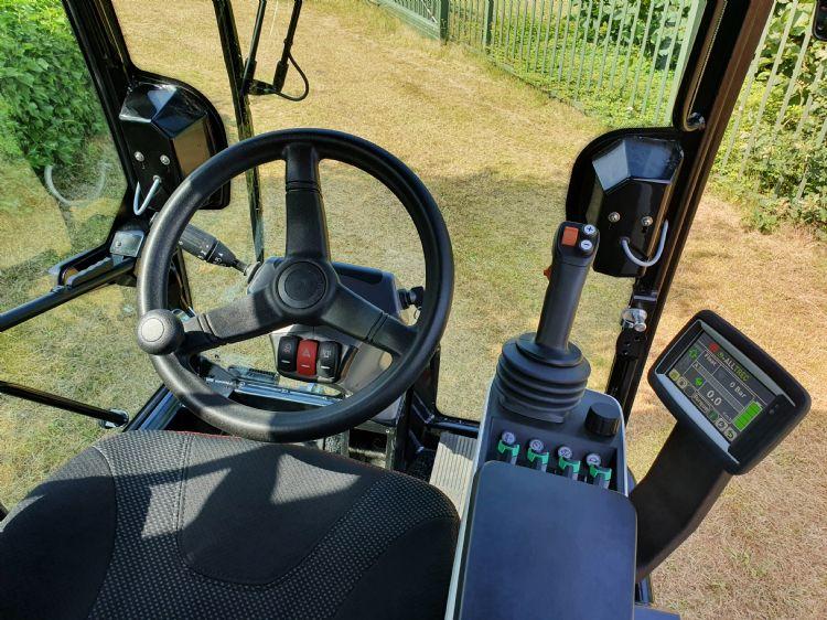Comfortabele cabine met mogelijkheden om de machine met fingertips dan wel met een joystick te bedienen.