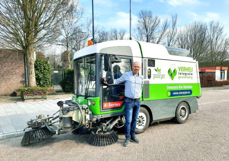 Paul Schouten bij de veegwagen op groen gras (CNG)